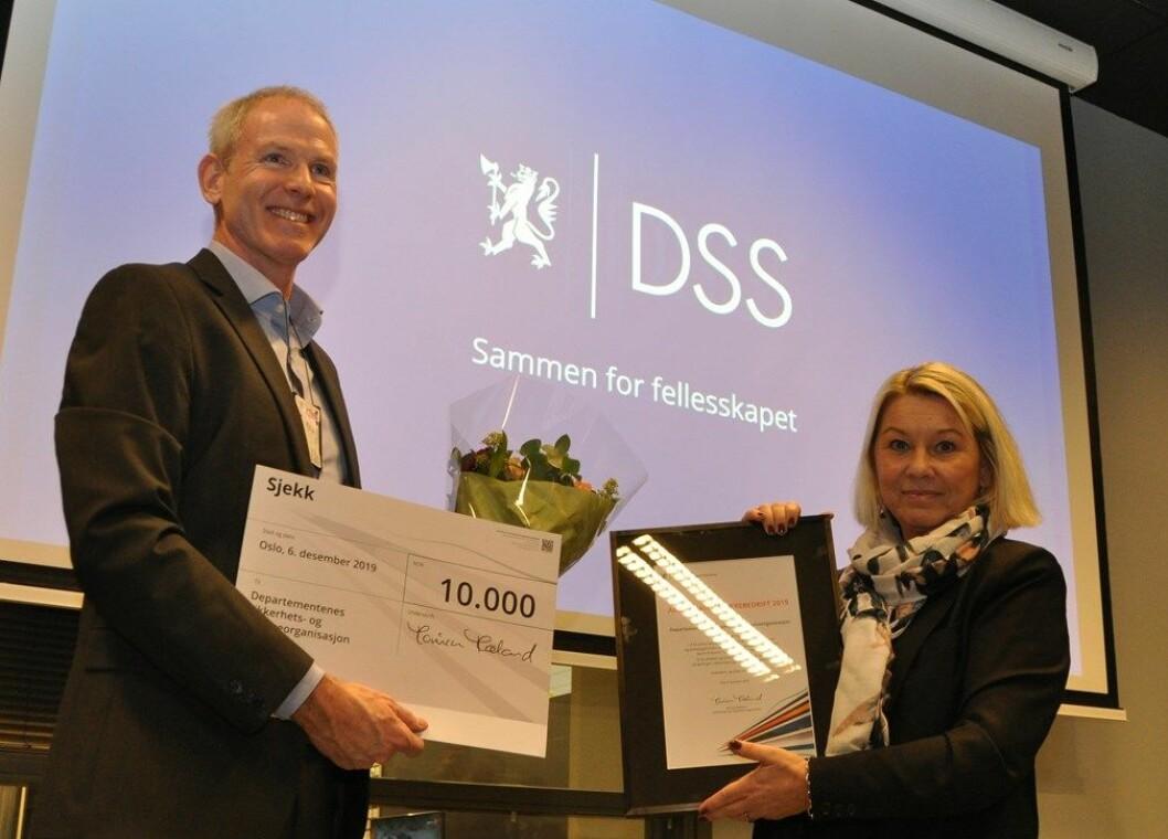 Kommunal- og moderniseringsminister Monica Mæland overrekker prisen til Are Langaard Jensen som som er avdelingsdirektør for sikkerhetstjenester i DSS. (Foto: Kommunal- og moderniseringsdepartementet)