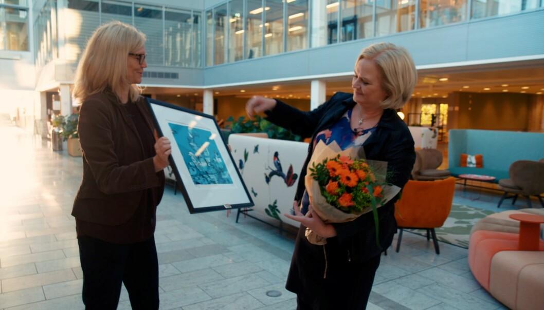 Nina Melsom Direktør for Arbeidsliv i NHO overrekker Akan-prisen 2020 til konserndirektør for HR og HMS i Hydro, Hilde Vestheim Nordh. Prisen er et bilde av kunstneren Gunilla Holm Platou og heter «Flokken».